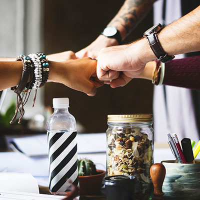 Zdjęcie przedstawiające zaciśnięte pięści złożone ze sobą w geście współpracy i porozumienia
