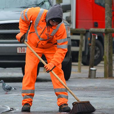 Zdjęcie przedstawiające mężczyznę w stroju roboczym zamiatającego ulicę