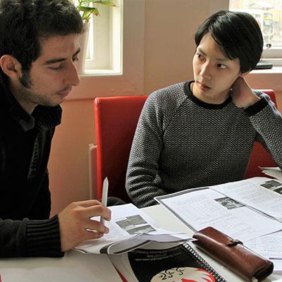 Zdjęcie przedstawiające nauczyciela uczącego ucznia - obcokrajowca, siedzących przy stole
