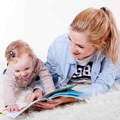 Zdjęcie przedstawiające matkę z małym dzieckiem przeglądających książeczkę dla dzieci