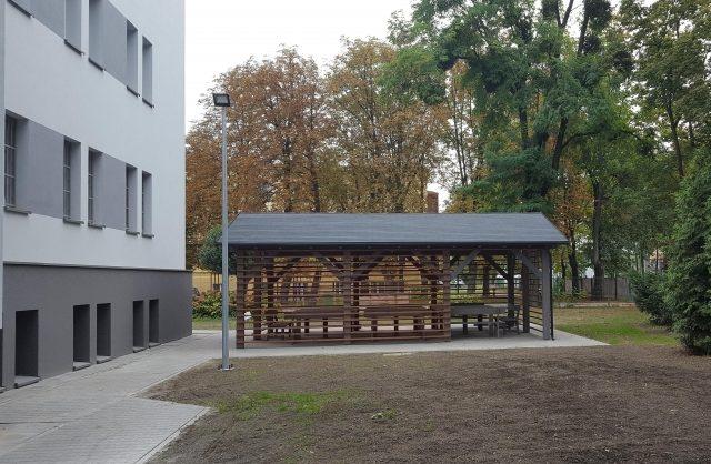 Zdjęcie przestawiające drewnianą altanę wybudowaną obok budynku