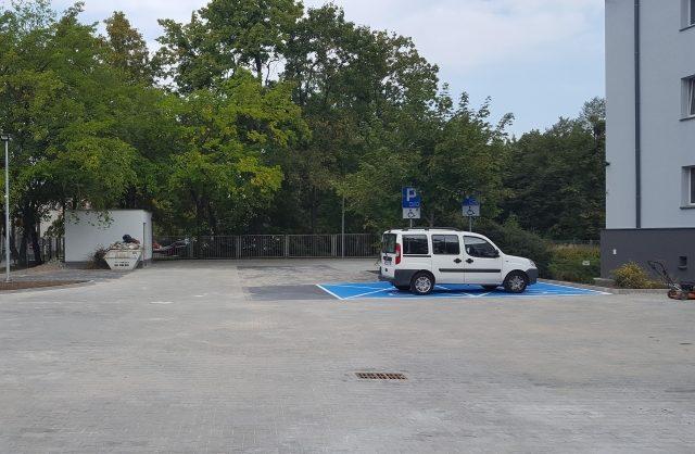 Zdjęcie przestawiające wyremontowany parking koło budynku